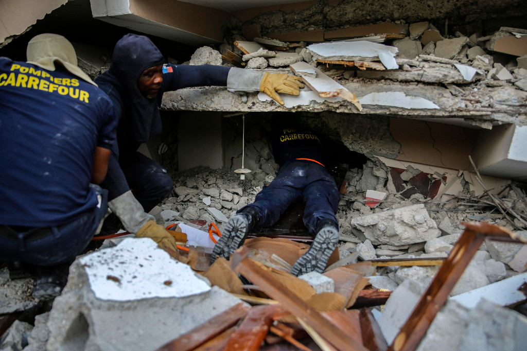Firefighters search for survivors amid the rubble in Haiti.