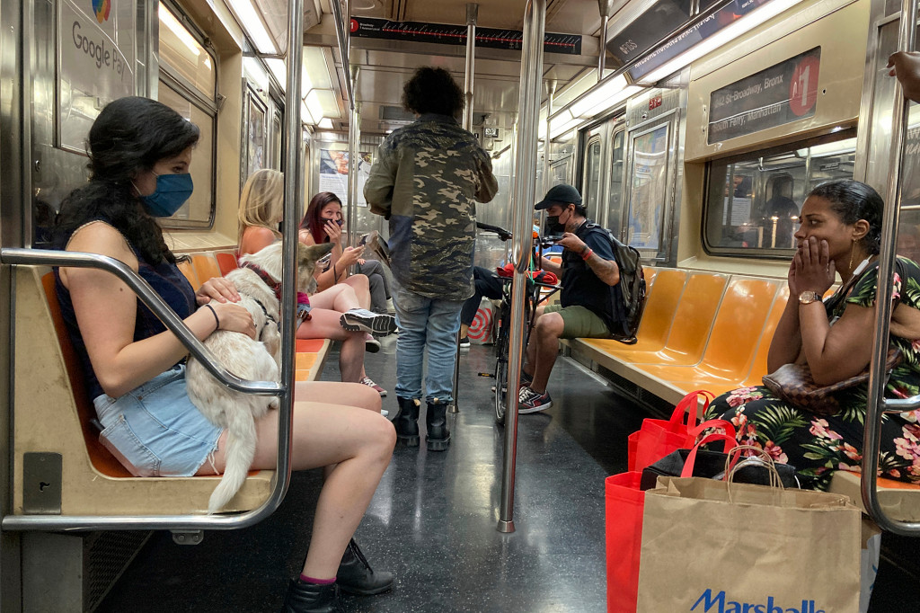 A woman wearing a face mask and holding a dog rides the subway in New York City on Saturday, July 31, 2021.